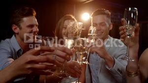 Group of smiling friends sitting on sofa and toasting a glasses of champagne