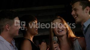 Happy friends singing songs together in a bar