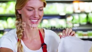 Female staff packing fruits in paper bag at supermarket