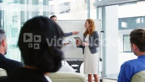 Businesswomen discussing on white board with coworkers