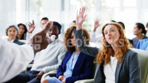 Businesspeople raising their hands during a meeting