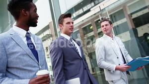 Business people interacting with each other while walking