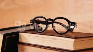 Stack of books with spectacles on a desk