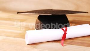 Close-up of graduation certificate with mortar board