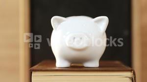 Close-up of books stack with piggy bank