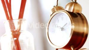 Close-up of paint brush with alarm clock