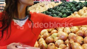Woman buying onion in supermarket