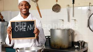 Chef holding showing open sign with chalkboard