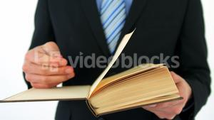 Mid-section of businessman flipping pages of book
