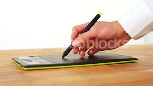 Hand of graphic designer using graphic tablet