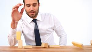 Businessman playing with building blocks
