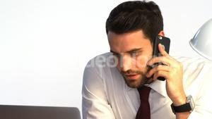 Businessman working at his desk and talking on mobile phone