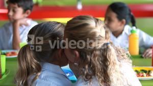 Schoolgirls whispering while having meal