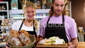Waiter and waitress holding a basket of bread and tray with sandwiches