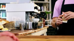 Waiter serving coffee to customer at counter