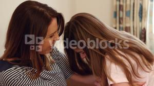 Mother and daughter having fun in living room