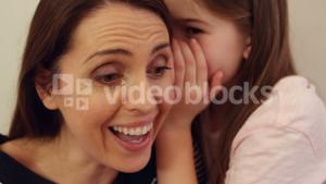 Daughter whispering in her mothers ear