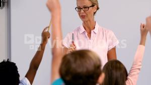 Kids raising their hands while teacher teaching them in classroom