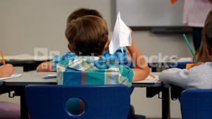 Boy throwing paper plane while teacher teaching in classroom