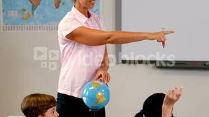 Teacher discussing over a globe with kids in classroom