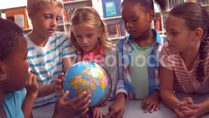 Kids studying over globe in library