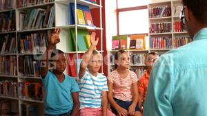 Kids raising their hands in library