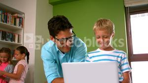 Teacher and schoolboy using laptop in library