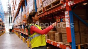 Female worker removing cardboard box from shelf