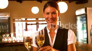 Female waitress serving a glass of champagne
