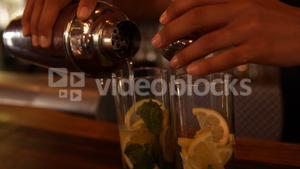 Hands of waiter pouring water on a glass