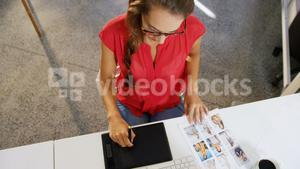 Female graphic designer using graphics tablet and computer