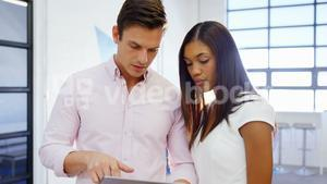 Business people discussing over digital tablet