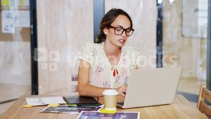 Frustrated female graphic designer using laptop