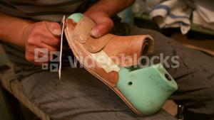Cobbler cutting a piece of leather on shoe last