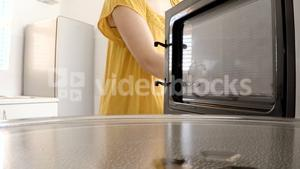 Woman putting a baking pan with sweet food to bake in oven