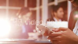 Businesswoman text messaging on mobile phone