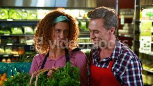 Smiling staff checking leafy vegetables in organic section