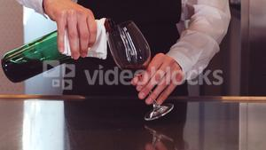 Bar tender pouring red wine in glass