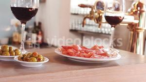 Glass of red wine and snacks on bar counter