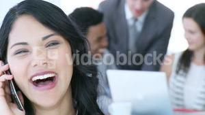 Businesswoman on mobile with her team working in office