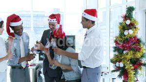Business team celebrating Christmas in office with champgane