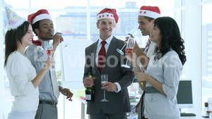 Business people celebrating Christmas in office while drinking champgane