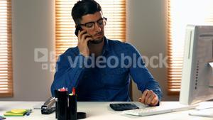 Male graphic designer talking on mobile phone
