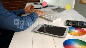 Male graphic designer using digital tablet while working on computer