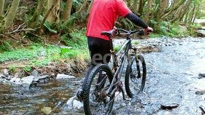 Mountain biker walking with bicycle in creek