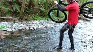 Mountain biker carrying bicycle while crossing creek