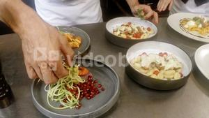 Mid-section of chefs garnishing food