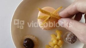 Hand of chef garnishing macaroon