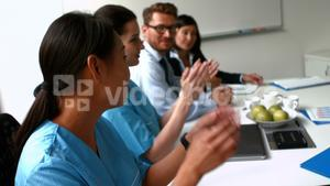 Team of doctors applauding during a meeting