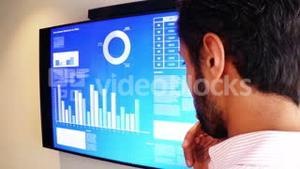 Male business executive looking at graph